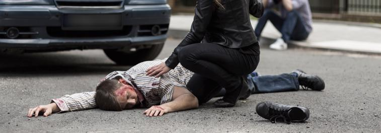 A woman attends to a pedestrian after he is hit by a car