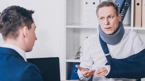 A man with a neck brace and cast on his left arm meeting with a lawyer in Pasadena to discuss a personal injury claim.